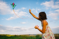 girl-playing-with-kite-in-field-PELY4X5.jpg